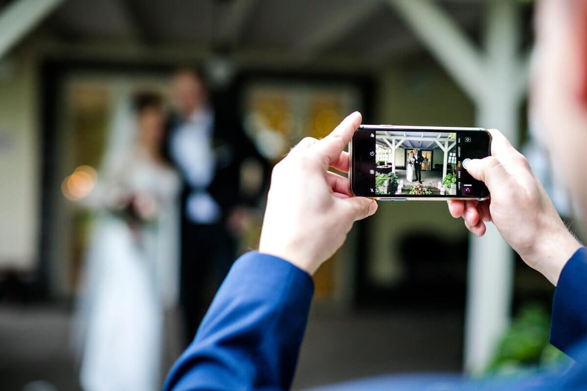 Esküvő fotózás során készült kép. Az párt fényképezi az egyik vendég.