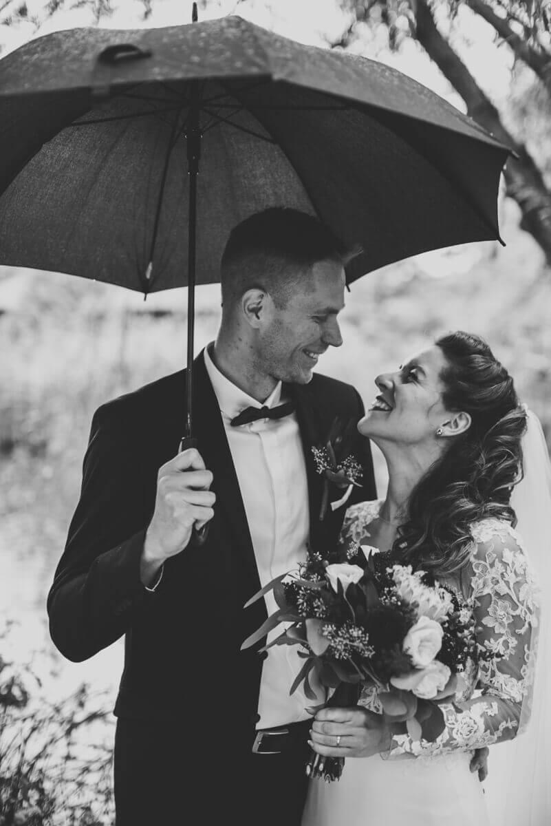 Esküvő fotózás során készült kép Lauráról és Balázsról, akik az esőben állnak és mosolyognak.