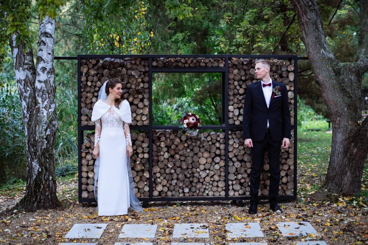 Esküvő fotózás során készült kép Lauráról és Balázsról, akik egymással szemben állnak egy fa fal előtt.