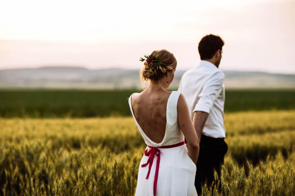 Esküvő fotózás során készült fotó Kingáról és Laciról állnak a mezőn háttal.