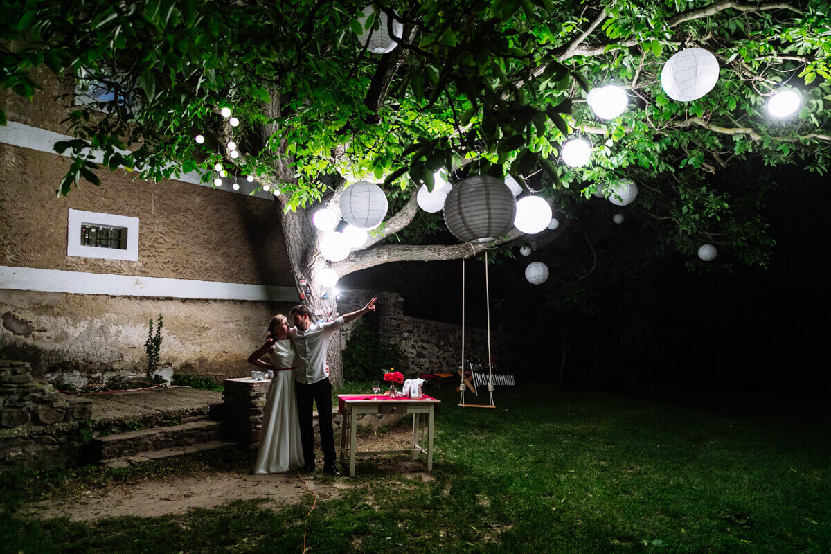 Esküvő fotózás során készült fotó Kingáról és Laciról miközben nézik a lampionokat.