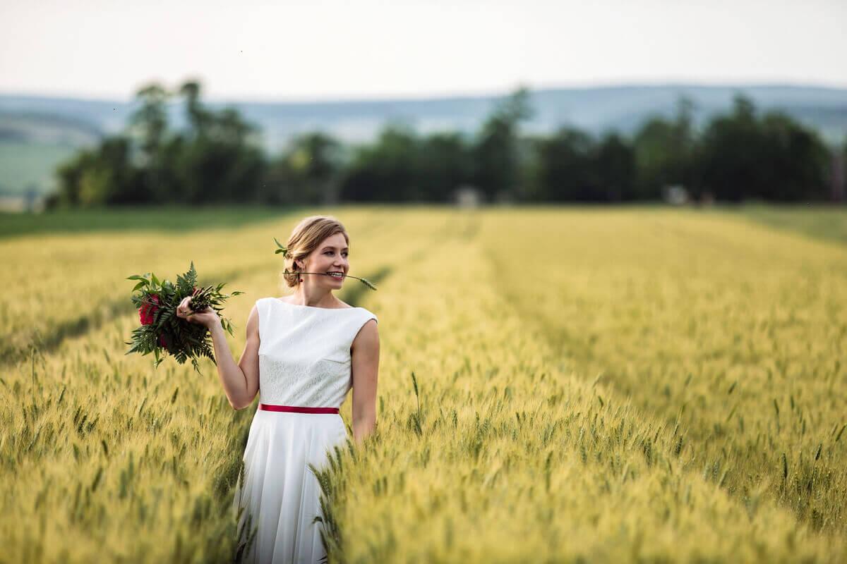 Esküvő fotózás során készült fotó Kingáról egy mezőn, kezében egy csokor.