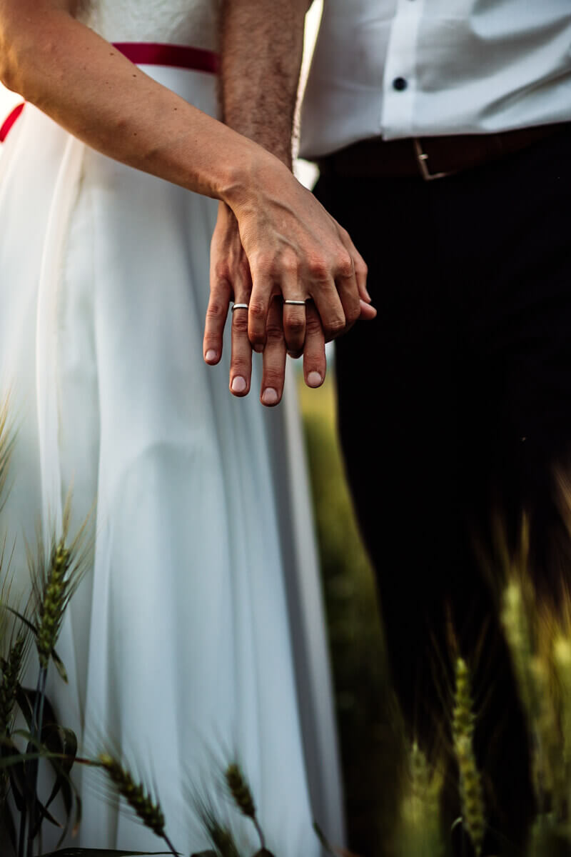 Esküvő fotózás során készült fotó Kinga és Laci fogják egymás kezét.