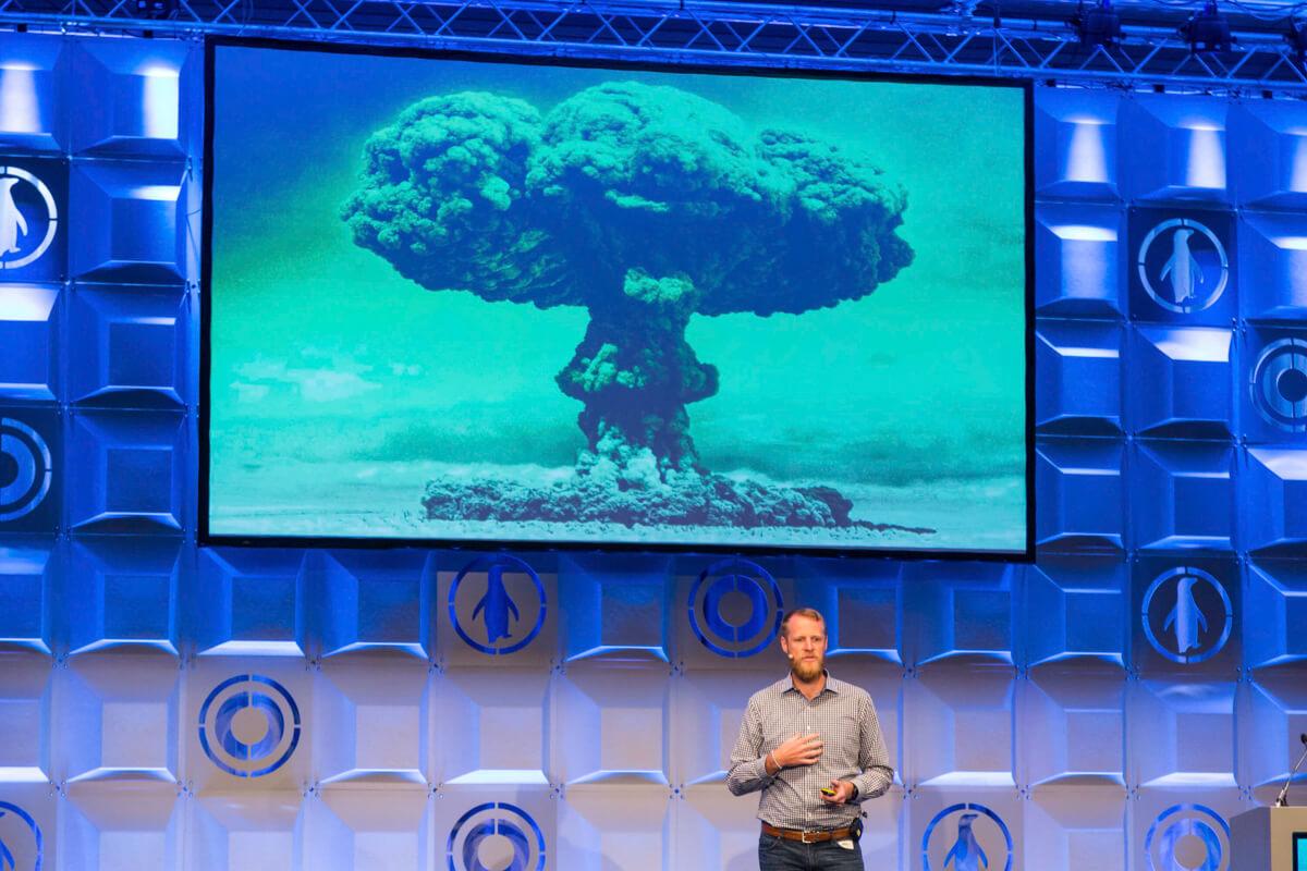 Rendezvényfotózás során készült kép egy eladóról, akinek a háta mögött egy atombomba kép van.