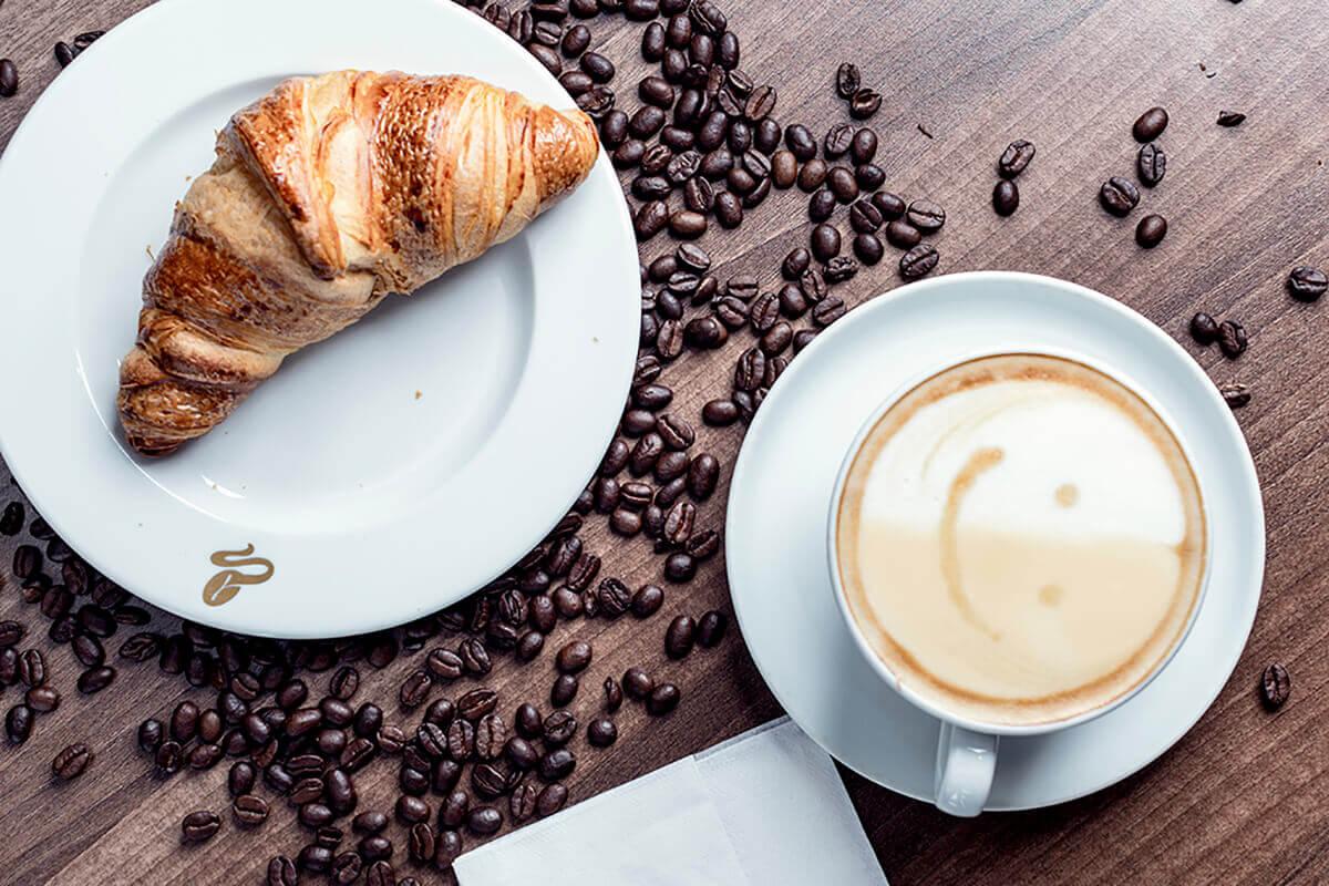 Reklámfotózás során készített termékfotó egy kávéról és egy croissantról.